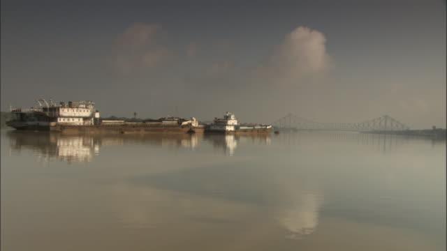 track along hooghly river past large boats, kolkata available in hd. - kolkata stock videos & royalty-free footage
