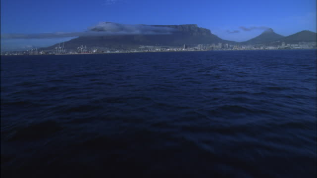Track along ocean towards Cape Town Harbour and Table Mountain Available in HD.