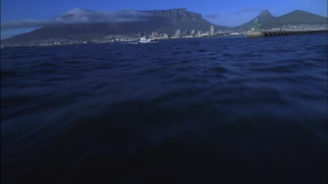 Track along ocean towards Cape Town harbour with Table Mountain in background Available in HD.