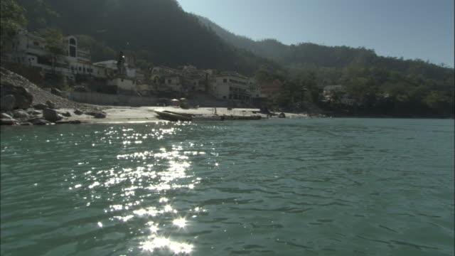 vídeos de stock, filmes e b-roll de track along river past buildings, rishikesh, india available in hd. - rishikesh