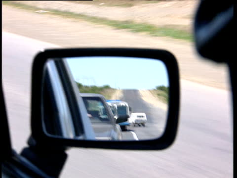 Track along road at speed as another car follows close behind in wing mirror South Africa