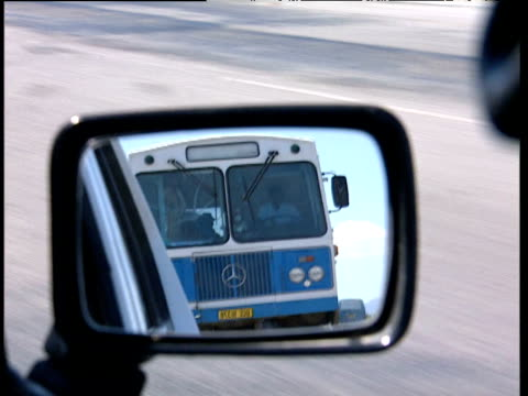 Track along road from car as bus approaches in wing mirror South Africa