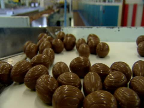 Track along side chocolate eggs as they wobble along factory conveyer belt and fall down slide