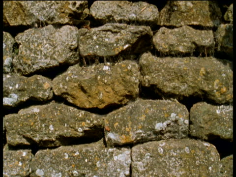Track along traditional dry stone wall then crash zoom into wall showing details of stone crevices and stonework