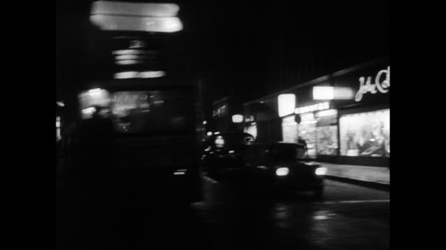 track along urban shop fronts at night; london, 1963 - moving past stock videos & royalty-free footage