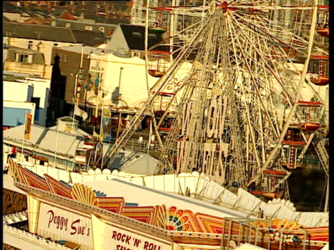 track around ferris wheel and amusements on pier blackpool - ブラックプール点の映像素材/bロール
