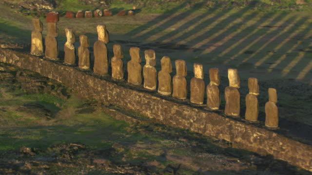 track around moai statues on ahu platform on rocky coast, easter island - maui stock videos & royalty-free footage