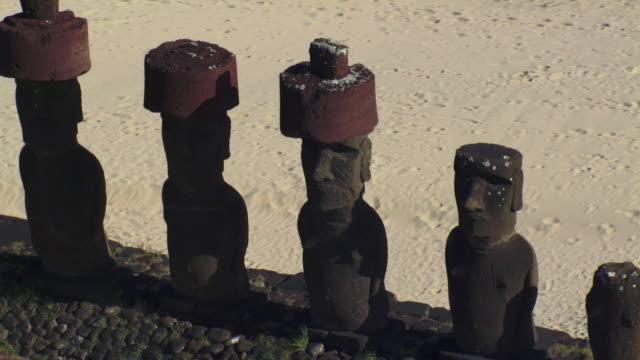 track around moai statues on ahu platform on sandy coast, easter island - maui stock videos & royalty-free footage