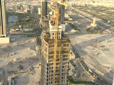 track around skyscraper under construction dubai - erezione video stock e b–roll