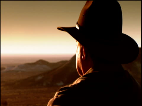 Track around the side and back of man's head with hat as he sits an gazes out over orange landscape at sunset.