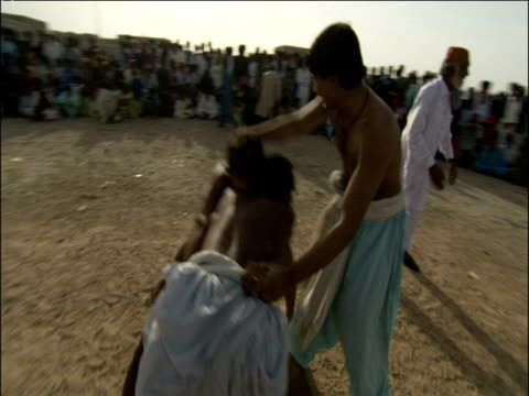 vidéos et rushes de track around traditional pahalwan wrestlers competing in dangal competition as crowd and referees watch pakistan - concurrent