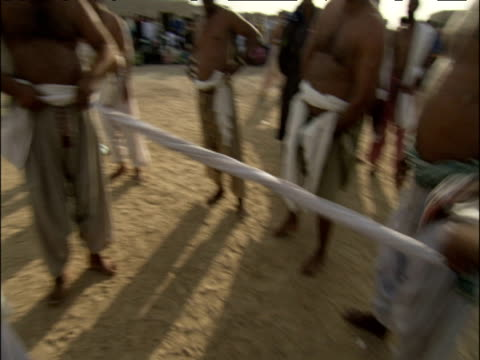stockvideo's en b-roll-footage met track around traditional pahalwan wrestlers wrap cloth in preparation for impending dangal competition pakistan - spelkandidaat