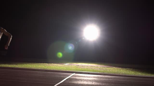 vídeos de stock, filmes e b-roll de a track athlete passes a baton to his teammate while running in a relay race. - revezamento