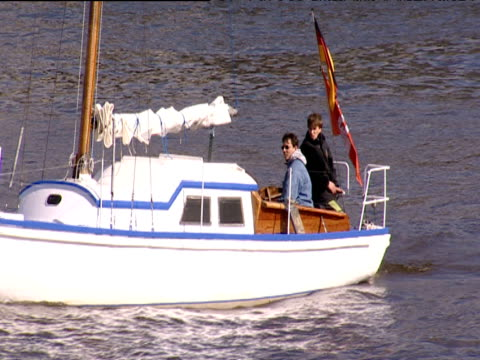 vídeos de stock e filmes b-roll de track away from small craft manned by two male sailors boat flies german flag and bobs up and down on choppy waters of river elbe hamburg - embarcação comercial