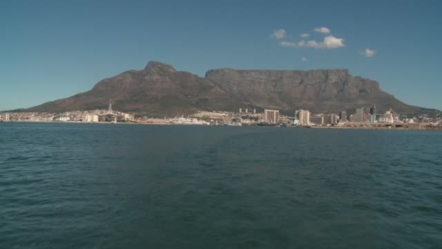 stockvideo's en b-roll-footage met track back across ocean with cape town skyline in distance available in hd. - rondrijden