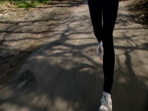track backwards as athlete runs along road england - menschliche gliedmaßen stock-videos und b-roll-filmmaterial