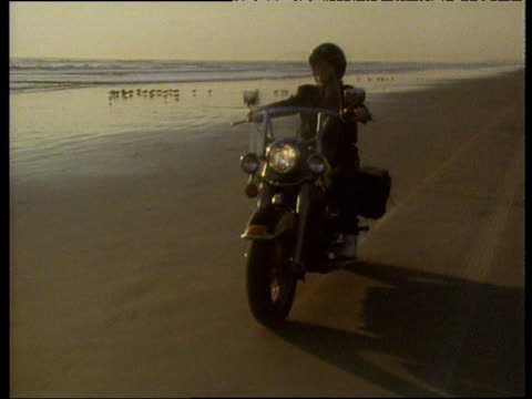 vídeos de stock, filmes e b-roll de track backwards as harley davidson motorcycle is ridden towards camera along sandy beach in golden evening light as sea laps shore in background - memórias