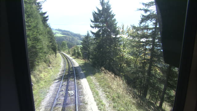 track backwards from train of schafberg mountain railway overlooking forests and wolfgangsee - オーストリア点の映像素材/bロール