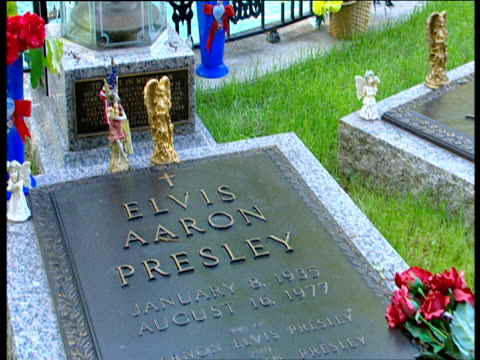 track backwards over elvis presley's grave stone flowers and angel ornaments graceland - tot stock-videos und b-roll-filmmaterial