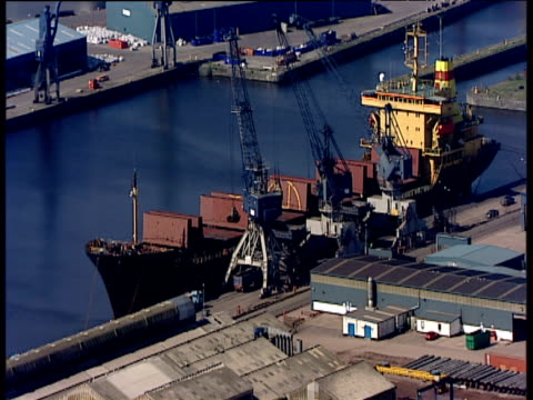 track backwards over leith docks from boat being unloaded by cranes edinburgh - edinburgh scotland stock videos & royalty-free footage