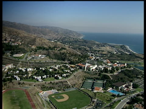 Track backwards over Malibu and surrounding area. Including houses swimming pools and baseball pitch sea in background
