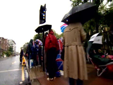 track backwards over people with umbrellas queuing to get into battersea park to see the river pageant for the celebration of the diamond jubilee - battersea park stock videos & royalty-free footage