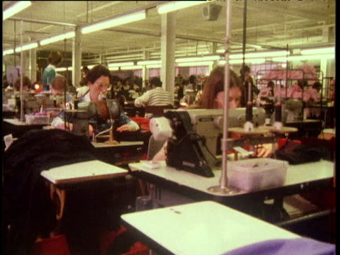 track backwards through large textiles factory as many women sew london 1970's - textile mill stock videos & royalty-free footage