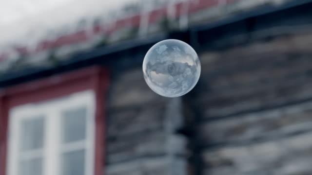 vídeos de stock, filmes e b-roll de track bubble floating near snow-covered house - caixilho de janela