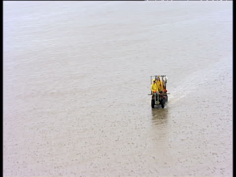 vidéos et rushes de track following cocklepickers riding on modified quad bike through shallow water morecambe bay - marée