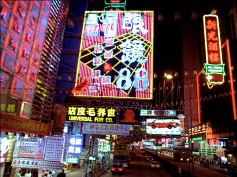 track forward along busy street below vibrant neon signs, hong kong - 1987 stock-videos und b-roll-filmmaterial