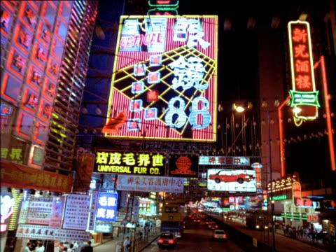 track forward along busy street below vibrant neon signs, hong kong - hong kong stock videos & royalty-free footage
