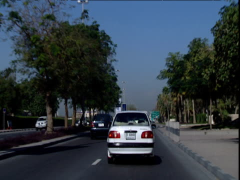Track forward along busy tree lined dual carriageway Dubai