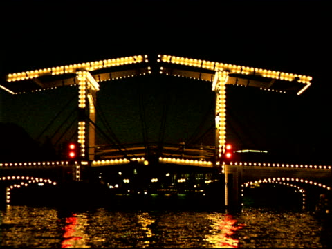 track forward along canal towards illuminated bascule bridge, amsterdam - bascule bridge stock videos and b-roll footage