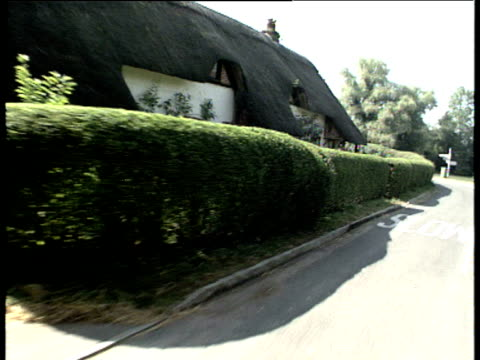 track forward along country lane over pond and thatched cottage crawley hampshire - tetto di paglia video stock e b–roll