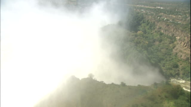 track forward and left over bridge across devil's gorge through mist at victoria falls, zimbabwe - victoria falls stock videos and b-roll footage