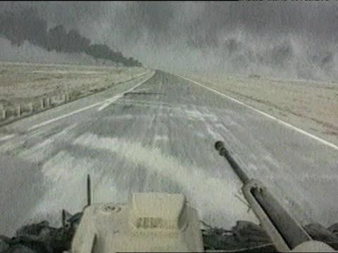 vídeos de stock, filmes e b-roll de track forward as tank drives down road toward smoke in distance during iraq war 26 mar 03 - guerra do iraq