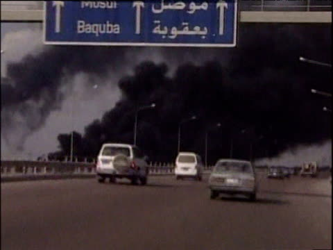 Track forward as traffic on motorway passes by thick black smoke from oil fields on fire Iraq Mar 03