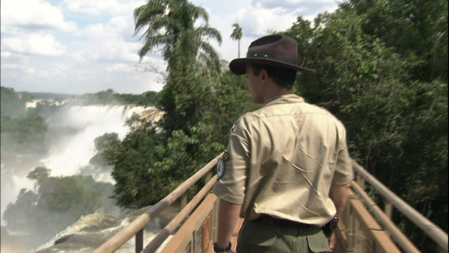 vídeos y material grabado en eventos de stock de track forward behind park ranger walking along public walkway, tilt down to rainbow in mist from iguazu falls, border of brazil and argentina - cataratas del iguazú