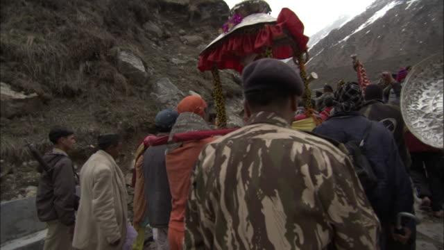 track forward behind pilgrims carrying shiva effigy towards kedarnath, india available in hd. - effigy stock videos & royalty-free footage