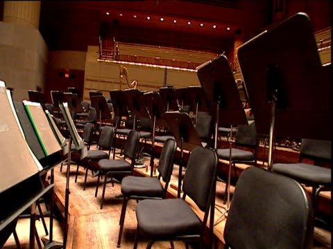 Track forward between chairs and music stands on raked orchestra stage