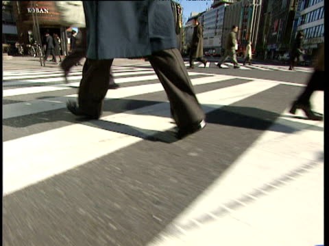 track forward following businessman crossing pedestrian crossing in ginza district of tokyo - aktentasche stock-videos und b-roll-filmmaterial