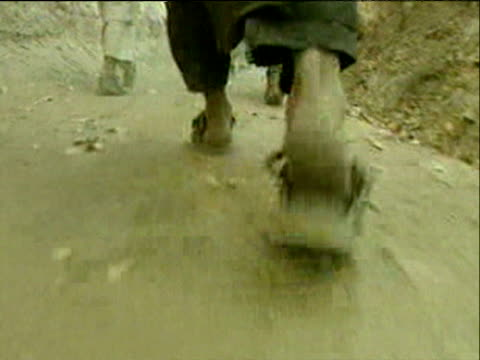 vidéos et rushes de track forward following feet of northern alliance soldiers walking along dusty path war in afghanistan 2001 - guerre d'afghanistan : de 2001 à nos jours