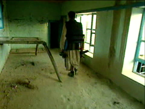 vidéos et rushes de track forward following northern alliance soldier carrying rifle while walking through abandoned house zoom in to graffiti on wall depicting tank and... - guerre d'afghanistan : de 2001 à nos jours