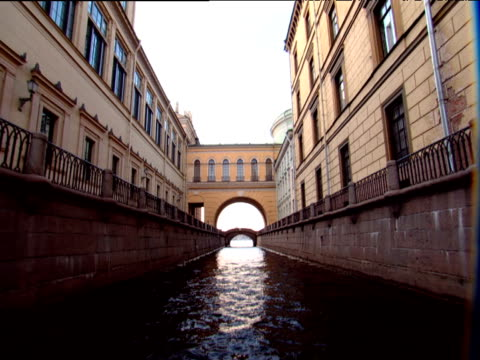 Track forward from boat along canal and tilt up under yellow archway and buildings St Petersburg