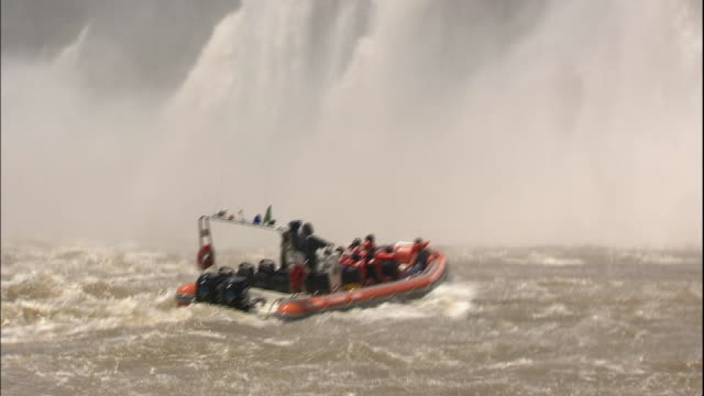 Track forward from boat following two other boats approaching base of Iguazu Falls, border of Brazil and Argentina