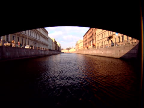 track forward from boat out from tunnel and along canal with buildings on embankments st petersburg - building storey stock videos and b-roll footage