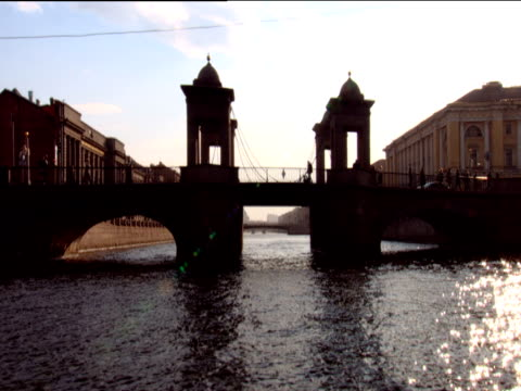 track forward from boat towards and under small silhouetted bascule bridge with pedestrians st petersburg - bascule bridge stock videos and b-roll footage
