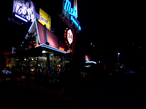 Track forward from car along strip past neon lit 24 hour drive in diner Sunset Strip Los Angeles