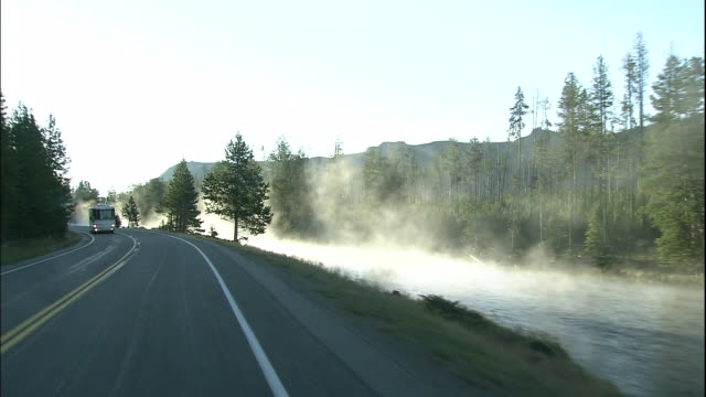 track forward from car alongside steam rising from firehole river in norris geyser basin - wyoming stock videos & royalty-free footage