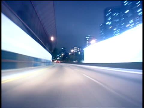 Track forward from car through city streets at night Hong Kong